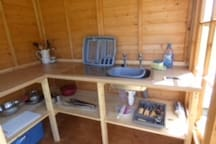 New Garden Kitchen with hot and cold water, Coleman extreme coolbox with ice blocks, gas hob and kitchen ware.