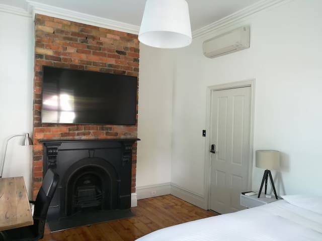 King room with exposed brick fireplace, and television with Amazon Fire TV for streaming in every room.