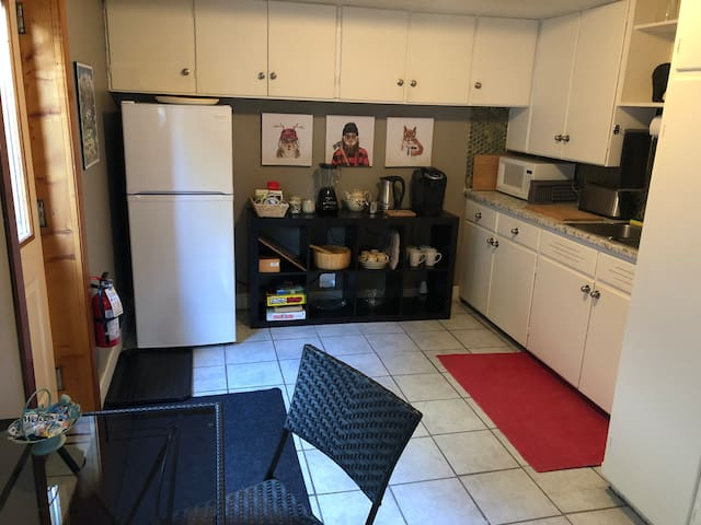 Kitchen with fridge, microwave, coffee and tea station, toaster, blender, cutlery, flatware, ice bucket, ice trays, wine and champagne glasses.