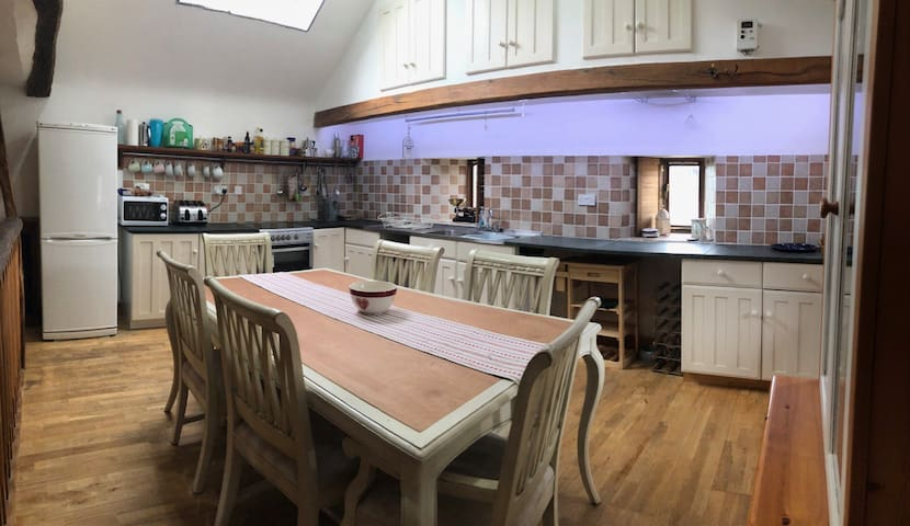 Kitchen , a large communal table and six chairs to eat and socialise around. Microwave a Toaster and all the basics for feeling at home ( porridge, sauces , salt n pepper t n coffee , everything you need to get on with cooking a meal.washing up materials are on hand for you.)