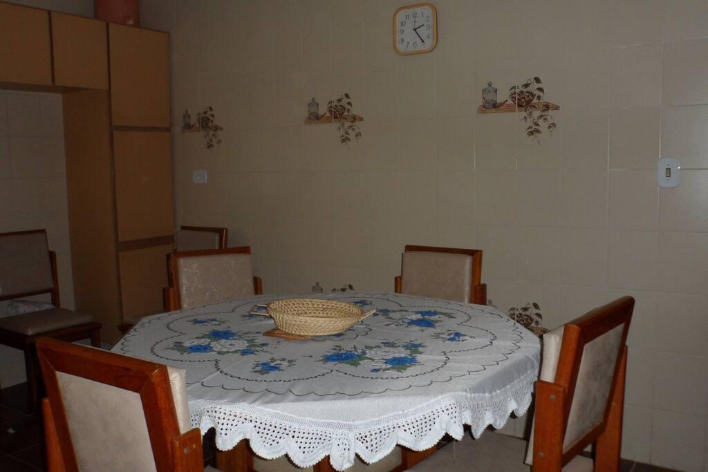 cozinha com ármarios, louças, filtro, talheres,pia, fogão, mesa, cadeiras, microondas, panela elétrica de arroz