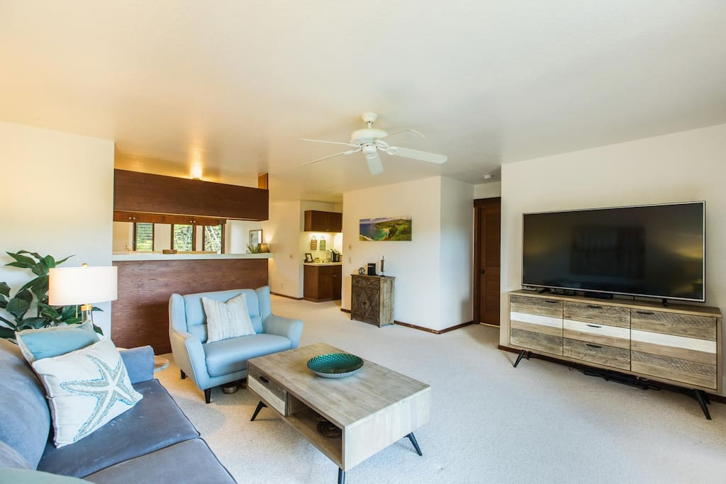 Open concept living area with large 65 in flat screen TV w/ cable