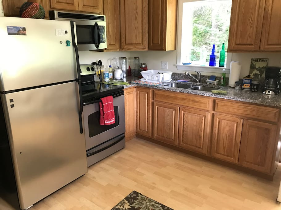 A fully equipped kitchen with granite countertops and a sunny table by the window.