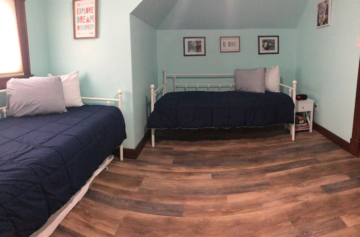 Upstairs bedroom with two twins, one has a trundle underneath. Closet in this room has extra bedding and pack n play.