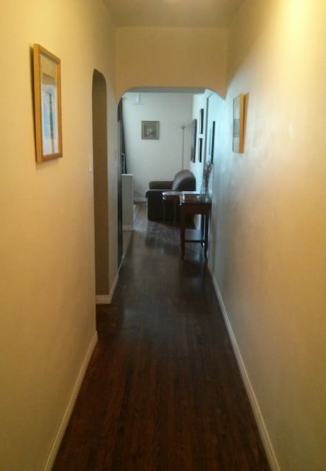 Come on in (view from suite entrance)! Original hardwood floors and 1950's archways. Closet at entrance (not shown) includes hangers, iron, ironing board, clothes drying rack, laundry detergent (for up to 5 loads), shoe/boot tray, hanging shoe/accessory organizer.