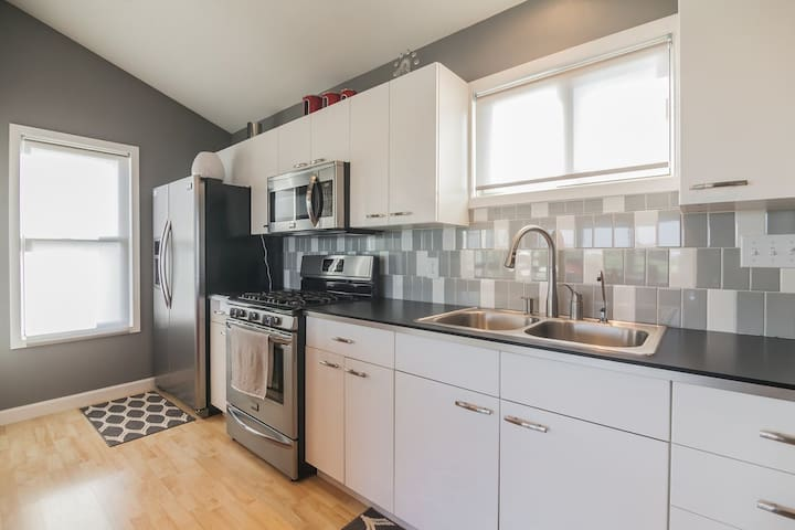 Modern kitchen equipped with RO purified water, dishes, cookware, flatware, toaster, microwave, oven, stove top, coffee maker, full sized refrigerator, kitchen tools, and more.