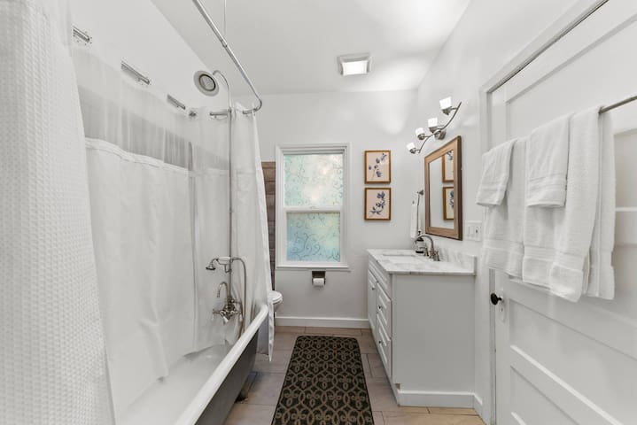 Full size bathroom with claw foot tub and shower