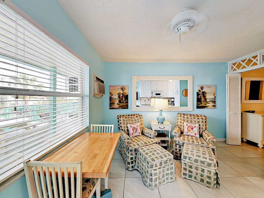 Airy with a Key West vibe, the living room has seating for two. Professional cleaning services provided by TurnKey.