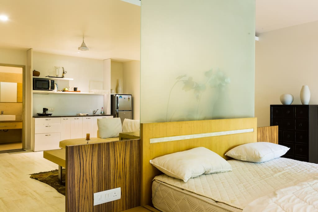 Bed with kitchenette in the background