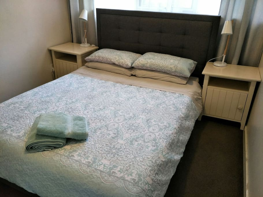 Plush queen sized bed, mirror door wardrobes, bedside tables with lamps.