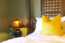 Comfortable bedding and option to purchase Hawaii volcano filtered water, among other items in our breakfast bar.