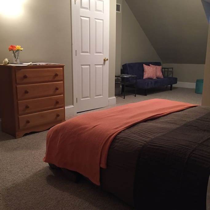 Bed and dresser, futon in opposite side of room