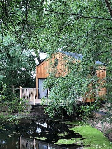 Cabane autonome au-dessus d'un étang en Bretagne
