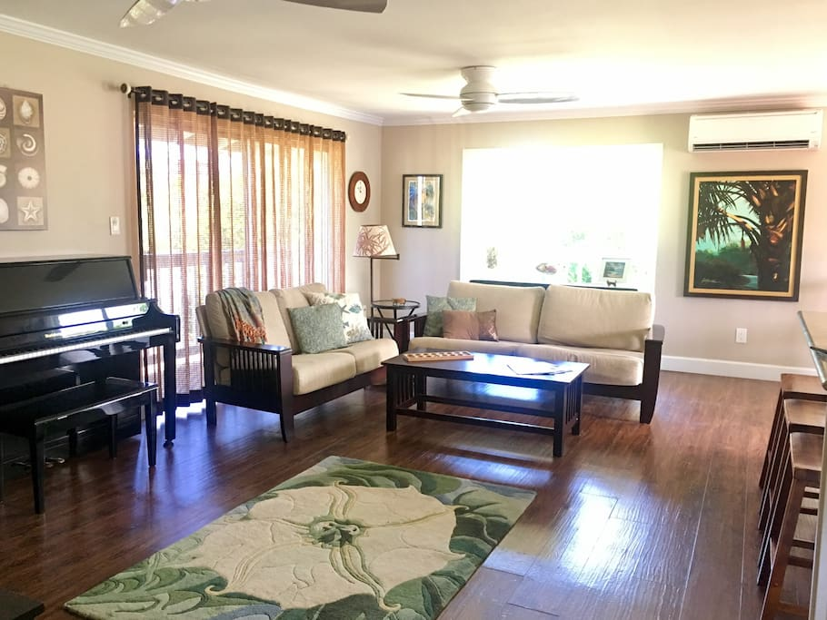 The living room area is open to the kitchen, has a piano, ukulele, books, tv, and yoga mats for use. The room is beautifully decorated with the tropics in mind and the home has a whole house fan and split AC unit for cooling purposes.