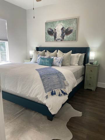"""Betsy's Room is my personal favorite. I love the welcoming Betsy portrait. She shares a bathroom with Frenchy's Room. Betsy has a firm mattress and luxury linens. She has all the streaming channels set up on the 43"""" television."""