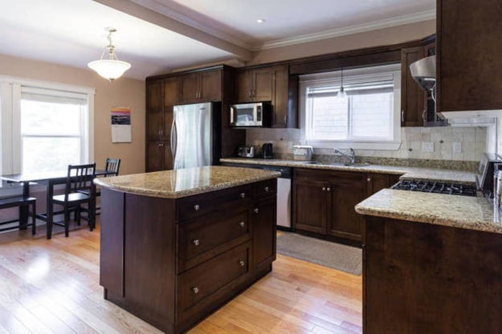 Kitchen with stainless steel appliances, hardwood floor, dishwasher, and gas stove. Breakfast nook seats up to 6.