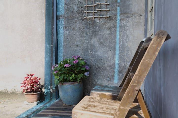 一对闲置的旧年小折椅,搭配周围亚热带花植,突显时光停滞的悠闲