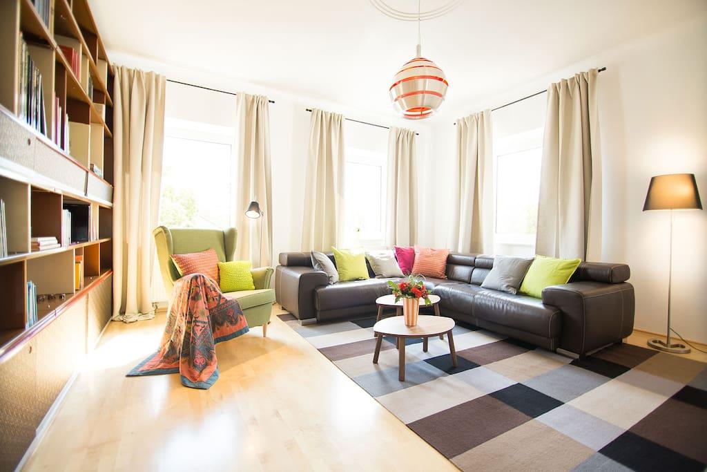 Das Wohnzimmer im Gunther49 ist mit einem Designerregal aus lackiertem Metall in Einzelanfertigung und einem in den Sitzflächen elektrisch verstellbaren italienischen Designerecksofa aus braunem Leder der Marke CALIA ITALIA ausgestattet.