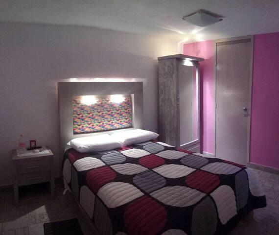 Rosa confortable habitación cerca del centro.