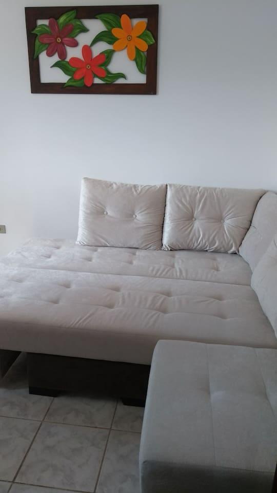 sofá em sala/cozinha onde dorme um adulto