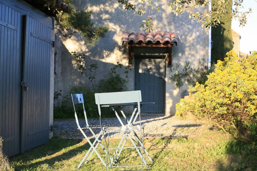 Une partie du jardin avec l'entrée de la maison
