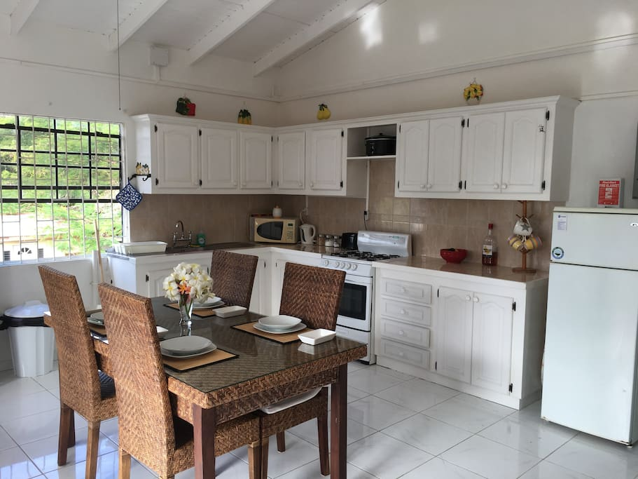 Generously spacious open plan kitchen with lots of storage units, gas cooker, fridge freezer, double drainer sink, microwave, toaster, electric kettle and full crockery and pans sets.