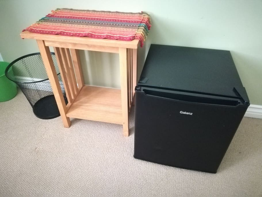 Mini fridge and small table in room for your convenience.