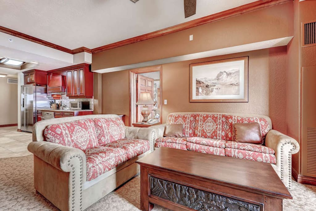 Spacious living room with fireplace, comfortable seating, HDTV  balcony; facing gourmet kitchen with stainless steel appliances.