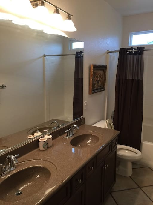 Shared bathroom with tub, shower and granite counter tops with double sinks