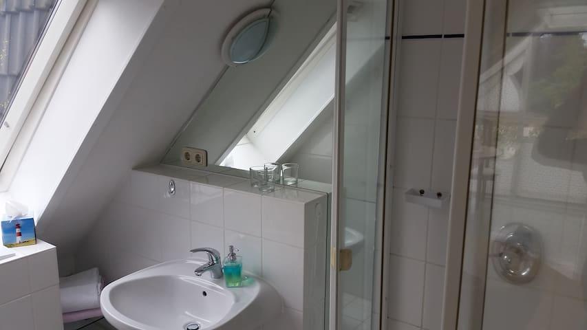 Blick ins Duschbad mit Fußbodenheizug und Handtuchheizung