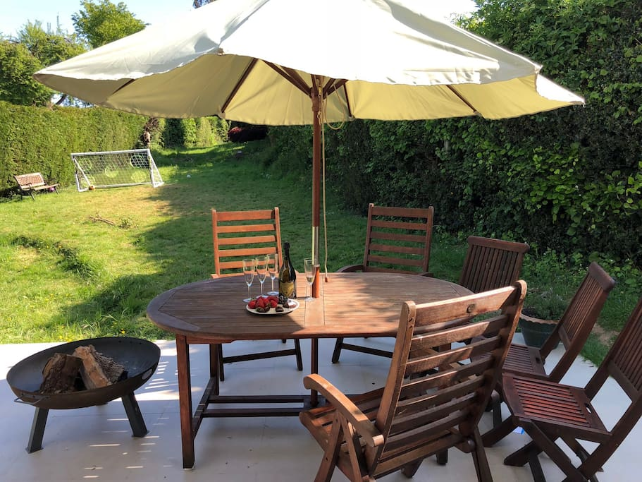 Garden table with parasol on terrace overlooking the garden