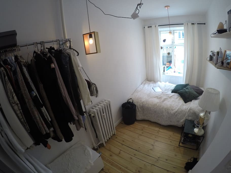 Smaller bedroom, queen sized bed, full length mirror, clothes rack