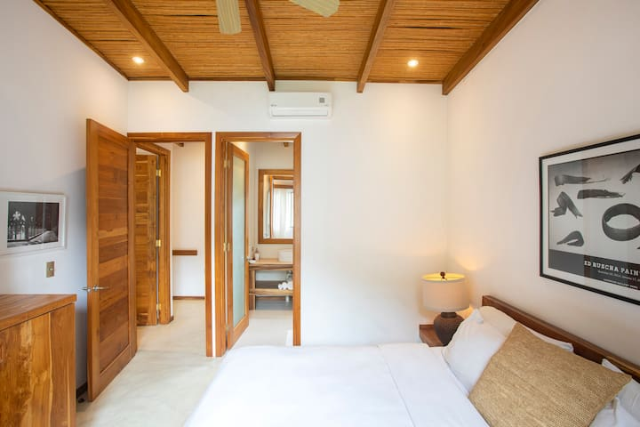 Second master bedroom with King size bed, en suite bathroom and a personal AC unit.