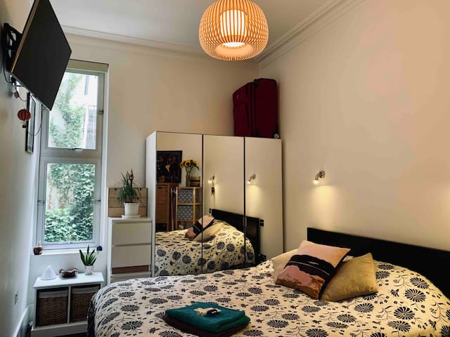 The bedroom has a wall mounted TV (Netflix/Prime logged in), comfortable king-size bed with memory foam topper, and en-suite bathroom with bath/shower. There is underfloor heating which can be controlled inside the room. Light switches beside bed.