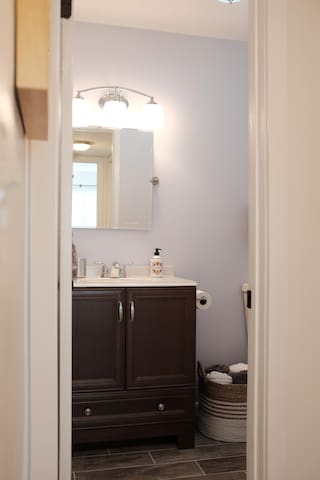 Bathroom is fitted with tile flooring, stand up shower, and restroom privacy.