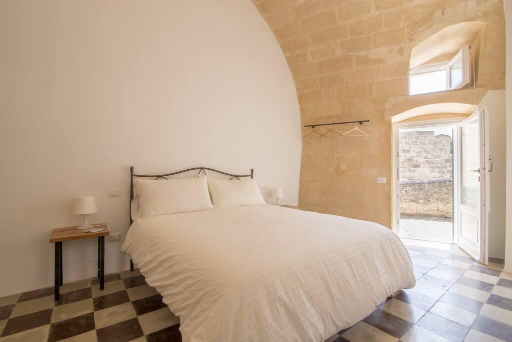 Camera con letto matrimoniale, dotata di finestre e porta finestra.