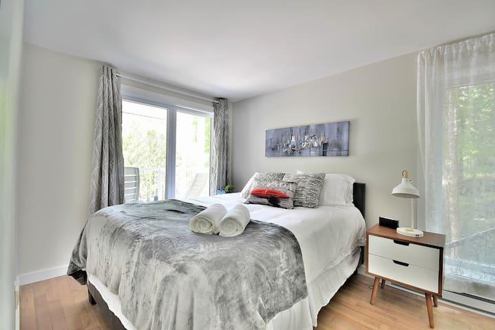Chambre avec lit queen,  grande fenestration qui vous offre une belle vue à l'extérieure