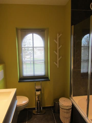 ruime badkamer met dubbele lavabo, ligbad met douchestang en douchescherm, toilet
