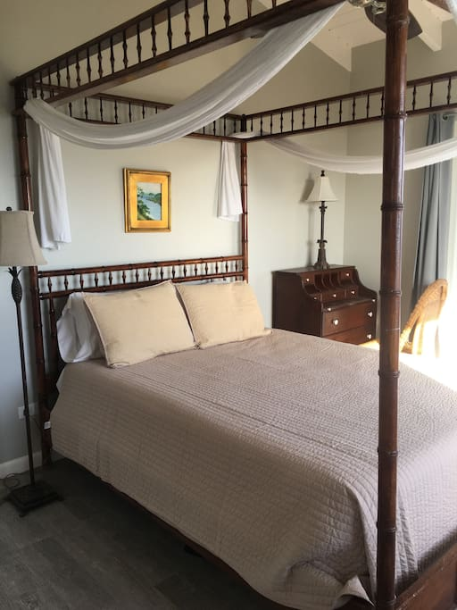 A comfy queen size bed with a fan overhead and ocean breezes.