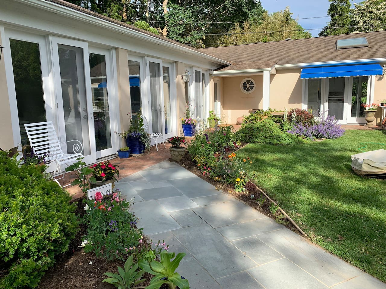 Walkway and door with screens that offer fresh air and great breeze all summer long. The garden is very new, still planting.