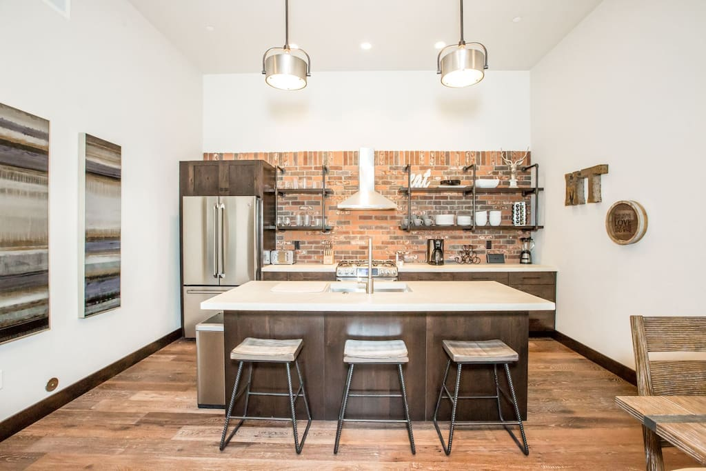 Open kitchen has stunning concrete countertops, brick backsplash & 3 barstools.