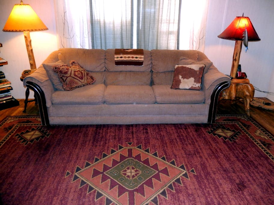 Living room with Native American design rug.  Cedar post lamps with leather shades.