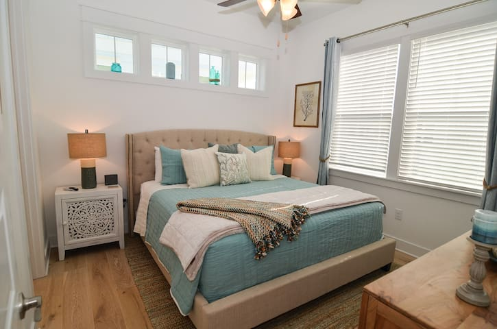 Master bedroom is furnished with a plush king bed