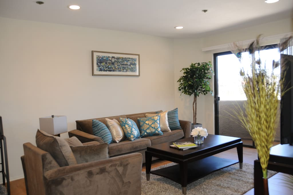 The living room is tastefully decorated with a comfortable sofa and chair. There is a balcony just off the living room. Not pictured is a working electric fireplace.