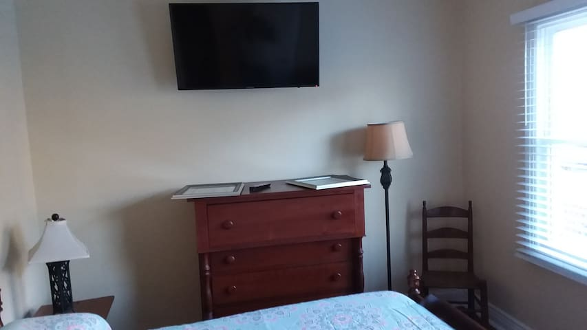 A TV is available in the bedroom. as well as a roomy cherry chest.