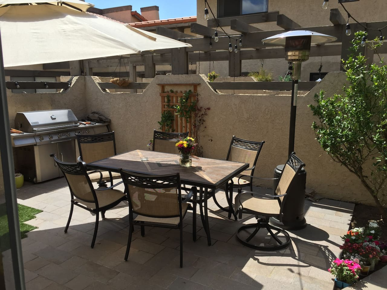 Beautiful private outdoor patio with large dining table for 6 guests, barbecue, heat lamp, garden, fountain, couch, and fire pit.
