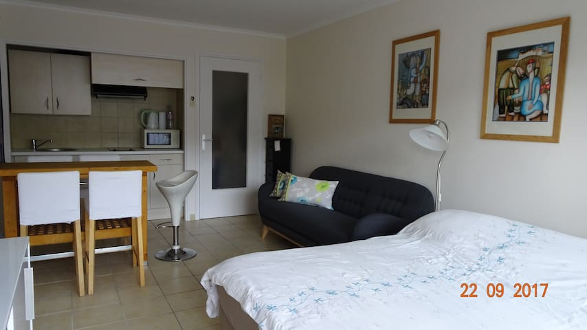 View of studio from the balcony with double bed, sofa and dining and kitchen area