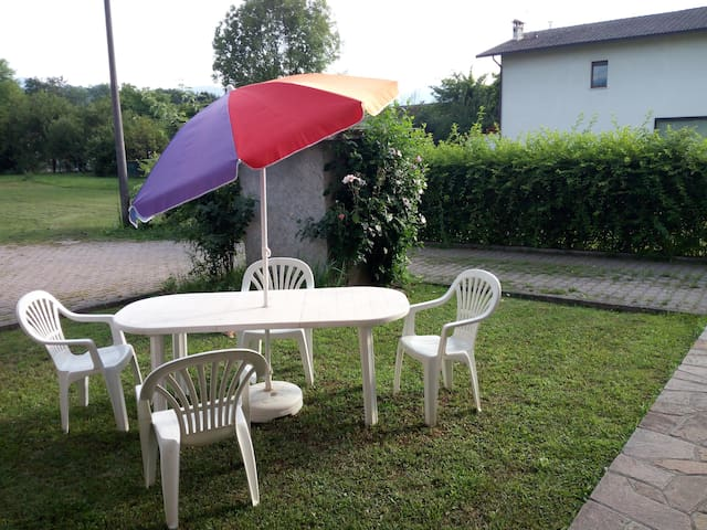 Giardino arredato con tavolo,sedie e ombrellini che gli ospiti potranno utilizzare gratuitamente
