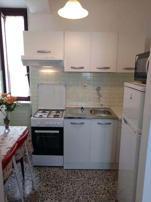 Cucina completa di angolo cottura fornello, forno a gas, frigorifero e forno a microonde.