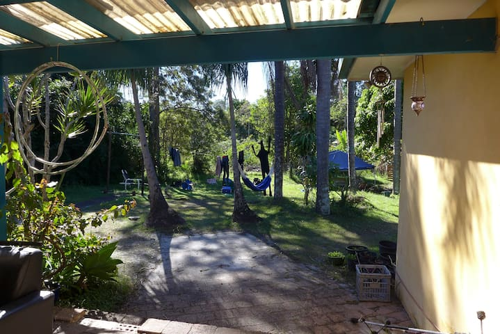 Giant backyard with multiple hammocks and a barbeque.